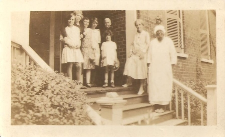 "Again at the Strahan house at the University of Georgia in Athens.  There's Matilda Basinger with her mother ""Batesie"", an unidentified woman, Genette, Garnett Basinger standing in front of her great-grandmother Margaret Roane Garnett Basinger, Mary ""Leslie"" Basinger Lawton, and Lillie."